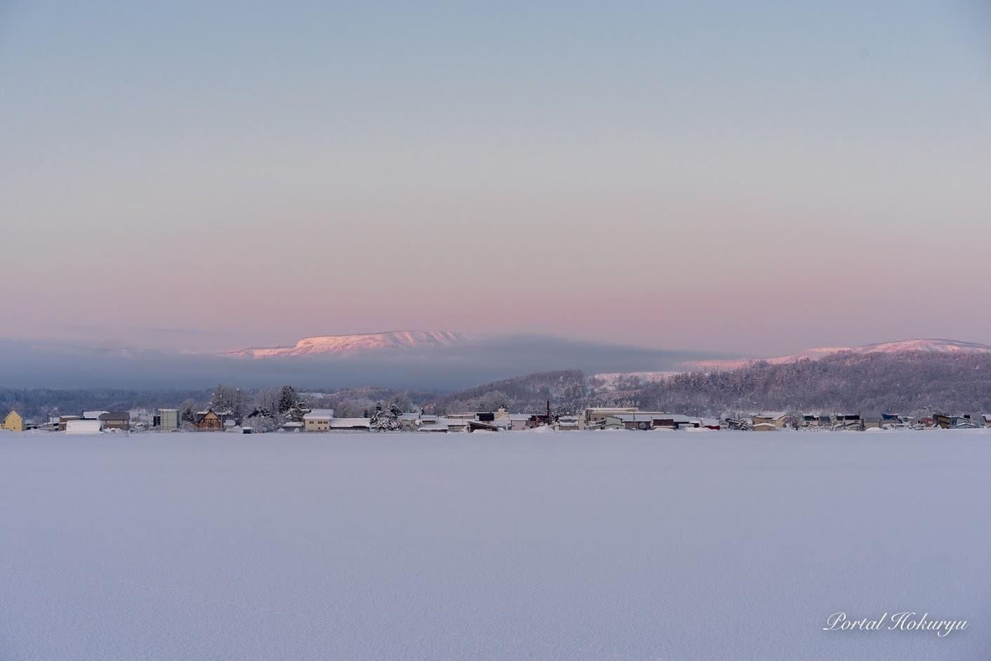 淡いピンク色に染まる恵岱岳